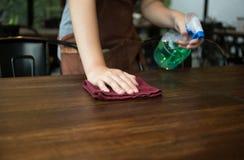 Serveuse nettoyant la table avec le désinfectant de jet Photographie stock