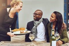 Serveuse servant un dîner de couples d'Afro-américain Photo stock