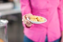 Serveuse servant un plat avec des biscuits Photo libre de droits