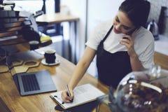 Serveuse travaillante de jeune étudiant mignon dans le café après des leçons Images libres de droits