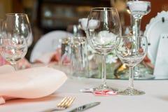 Serviço ajustado da tabela da restauração com pratas, guardanapo e vidro no restaurante antes do partido Foto de Stock Royalty Free