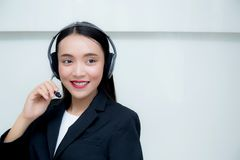Serviço ao cliente de sorriso da mulher asiática bonita que fala em auriculares fotografia de stock