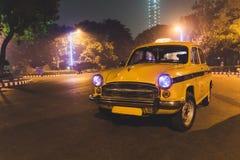Serviço clássico amarelo do táxi no estacionamento do aeroporto de Kolkata na noite Imagens de Stock Royalty Free
