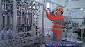 Serviço da fábrica, homem do técnico no capacete e equipamento da fábrica dos reparos do workwear com as ferramentas especiais pe video estoque