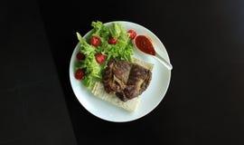 Serviço da faixa da carne com molho e alface fresca em uma placa na tabela de madeira Imagens de Stock