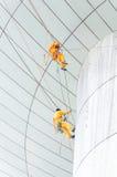 Serviço das janelas da limpeza na construção alta da elevação é perigoso Fotografia de Stock