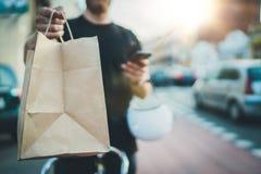 Serviço de alimentação rápido da entrega de Anonimous em casa O correio do homem entregou a ordem nenhum saco do nome com aliment fotos de stock royalty free