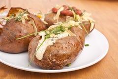 Serviço de batatas com manteiga cozidas Fotografia de Stock