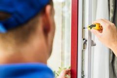 Serviço de manutenção da janela - o trabalhador que ajusta o quadro parafusa Fotos de Stock