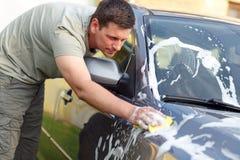 Serviço do auto da lavagem de carros - equipe o carro de lavagem com uma esponja e uma espuma Fotografia de Stock Royalty Free