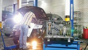 Serviço do carro Posição do homem do mecânico pelo carro com capa aberta e verificação do óleo filme