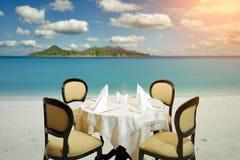 Serviço do jantar da praia na luz do por do sol Imagens de Stock