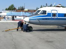 Serviço do russo Antonov an-38 nos trabalhadores do técnico do aeródromo imagens de stock
