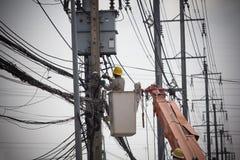 Serviços de reparações do cabo de fiação dos eletricistas Técnico que verifica fio elétrico quebrado da fixação no polo fotografia de stock