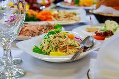 Servi à la table de banquet Verres de vin avec des serviettes, verres et salades Images stock