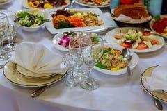 Servi à la table de banquet Verres de vin avec des serviettes, verres et salades Photographie stock