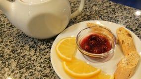 Service à thé de la théière et de la soucoupe blanches de porcelaine, à côté des biscuits, des tranches de citron et de la confit clips vidéos