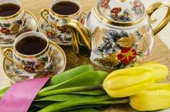 Service à thé de porcelaine avec les fleurs jaunes de tulipe Photographie stock