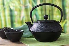 Service à thé vert asiatique avec la bouilloire noire de porcelaine sur le tapis en bambou avec le thé vert sec dans la cuvette C Photos libres de droits
