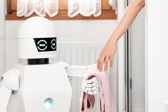 Robot is giving a towel to an women. Service Ambient Assisted Living robot is giving a towel to an women under the shower in the bathroom Royalty Free Stock Photography