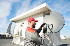 Service-Arbeitskraft, die Satellitenantennenteller für Kabelfernsehen installiert und passt lizenzfreies stockfoto