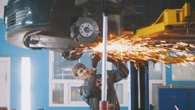 Service automatique de voiture - la construction de meulage en métal de travailleur avec une circulaire a vu sous le fond du véhi Photo stock