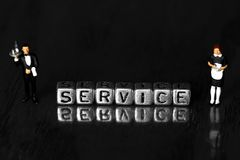 Service on beads with a scale model waiter and waitress standing next to word. On wooden background royalty free stock photography