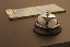 Service bell. Hotel service bell with map  on table Stock Photos