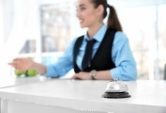 Service bell and female receptionist Stock Photography