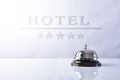 Service bell on hotel reception with Hotel placard background. Hotel service bell on a table white glass and placard hotel and stars background. Concept hotel Stock Image