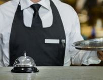 Service bell and the Waiter. In a restaurant with a tray in hand Royalty Free Stock Photo