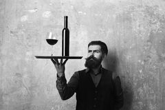 Service and catering concept. Man with beard and mustache. Holds wine on beige wall background. Waiter looks at glass and bottle of red wine on tray. Barman stock photo