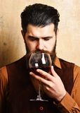 Service and catering concept. Sommelier with glass of red wine. Man with beard and mustache holds wine on beige wall background. Degustator with calm dreaming stock image