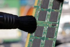 The service center worker cleans dust at Random Access Memory or electronic board RAM stock photos