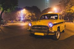 Service classique jaune de taxi au stationnement d'aéroport de Kolkata la nuit Images libres de droits