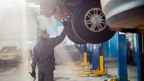 Service d'automobile de garage - un mécanicien vérifie la transmission Images libres de droits