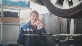 Service d'automobile de garage - une voiture près soulevée de mécanicien parle du téléphone portable Images stock
