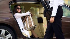 Service de luxe de taxi, portière de voiture d'ouverture de chauffeur pour le passager féminin, voyage image libre de droits