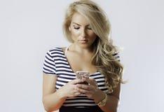 Service de mini-messages blond de fille de Latina au téléphone Photographie stock libre de droits