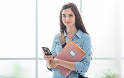 Service de mini-messages d'étudiant universitaire avec son téléphone Photo stock
