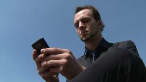 Service de mini-messages d'homme d'affaires sur le smartphone en parc clips vidéos