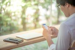 Service de mini-messages d'homme sur le smartphone dans l'espace de travail Photo stock