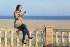 Service de mini-messages de femme dans un téléphone intelligent sur la plage Images stock