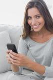 Service de mini-messages de femme tandis qu'elle est reposée sur un sofa photos libres de droits