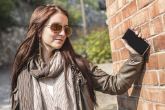 Service de mini-messages de fille à son téléphone portable avec le mur urbain dessus Image libre de droits
