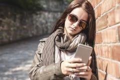 Service de mini-messages de fille à son téléphone portable avec le mur urbain dessus Photos libres de droits