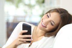 Service de mini-messages de fille à un téléphone portable à la maison photo libre de droits