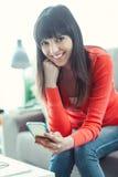 Service de mini-messages de sourire de femme avec son mobile images stock