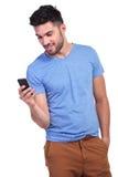 Service de mini-messages de sourire de jeune homme sur son smartphone photographie stock