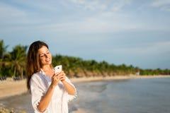Service de mini-messages de touristes femelle sur le smartphone à la plage tropicale images stock